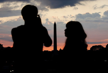A man takes pictures of the Washington Monument as a woman watches during sunset in Washington
