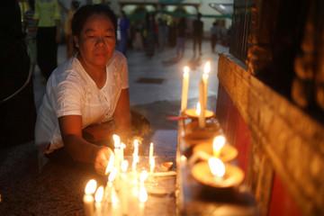 A woman lights candles at a pagoda during the Thadingyut festival in Mandalay