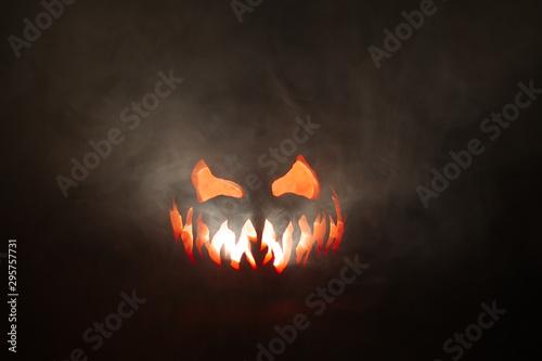 Scary Halloween jack o lantern face glowing in smoke.