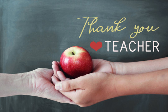Student and teacher hands holding red apple with chalkboard background, Happy teacher's day