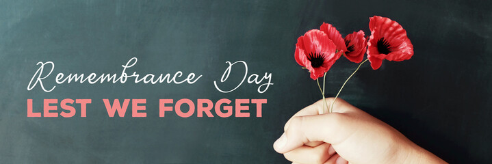 Fotobehang Poppy Hand holding red poppy flowers, remembrance day, Veterans day, lest we forget concept