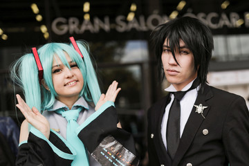 "A woman, dressed as ""Miku Hatsune"" and a man dressed as ""Sebastian Michaelis"" from Kuroshitsuji poses for photographs during the Leisure and Fantasy Lounge ""SOFA"" in Bogota"