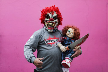 """A man wearing a clown mask, holds a Chucky doll while posing for photographs during the Leisure and Fantasy Lounge """"SOFA"""" in Bogota"""