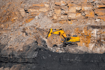 Open mine of gold, diamonds, coal. Industrial landscape with large yellow dump trucks and excavators