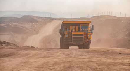 Open pit gold mine, big yellow mining truck moves ore