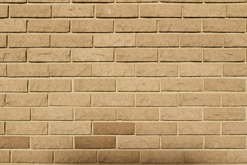 Tan color natural stone brick wall background with rounded rough texture blocks