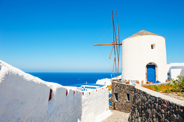 Old windmill in Oia town in Santorini island, Greece. Summer landscape with sea view. Travel destination, popular touristic resort