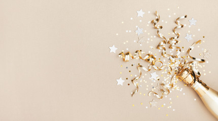 Celebration background with golden champagne bottle, confetti stars and party streamers. Christmas,...