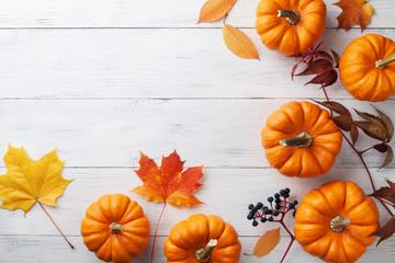 Autumn Thanksgiving background. Pumpkins and leaves on white table top view.