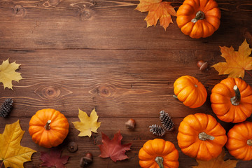 Autumn Thanksgiving background. Pumpkins, acorns and leaves on wooden board top view.