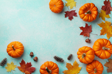 Autumn Thanksgiving background. Pumpkins and maple leaves on turquoise table top view.