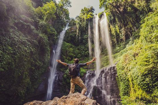 Man in turquoise dress at the Sekumpul waterfalls in jungles on Bali island, Indonesia. Bali Travel Concept