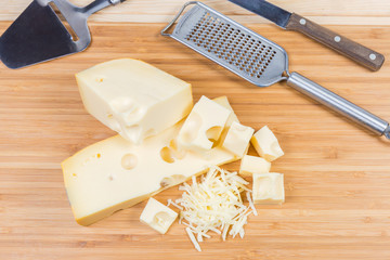 Sliced and grated Swiss cheese and slicers on cutting board