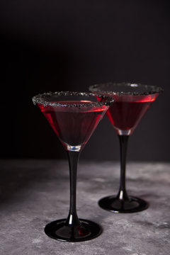 Two glasses with red cocktail for Halloween party on the dark background