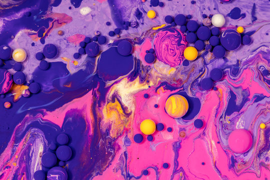 Acrylic paint balls abstract texture. Purple, blue and yellow liquids mix. Creative multicolor background. Bright colors fluid, flowing wallpaper design. Mixed pigments colourful backdrop.