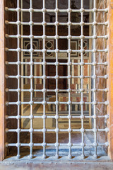 Wooden grunge window with iron grid revealing interior of Mausoleum of Sultan Barquq, Cairo, Egypt