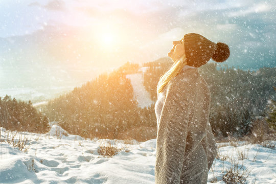 Portrait Happy woman traveler on the top of mountain and looking on beautiful winter snowy view.