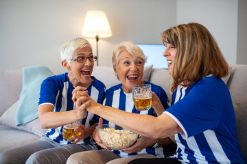 Senior women watching football on TV. Elderly Woman Fans Emotionally Watching Soccer on Tv and celebrating victory at home. Soccer team just scored a goal