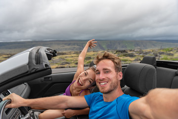 Wall Mural - Car couple taking selfie photo with phone on road trip driving cabriolet sports car on summer vacation with arms up in fun. Asian girl, Caucasian man dancing in open roof car.
