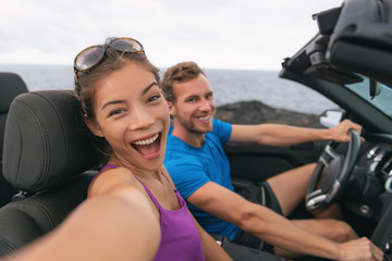 Wall Mural - Selfie car travel couple having fun on summer road trip vacation driving to holidays. Asian woman and man excited taking self-portrait photo with mobile phone.