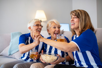 Football fans watching a game on tv. Sports fans rooting for their team. Elderly Woman Fans Emotionally Watching Soccer on Tv  and celebrating victory at home. Excited senior women watching a game