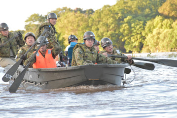 Rescue workers paddle a boat during evacuation operation after a typhoon swept through Kawagoe, Saitama prefecture