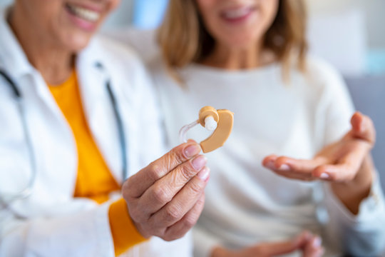 Mature female doctor hearing specialist in her office trying hearing aid equipment to a patient elderly senior woman. The doctor laryngologist explains to senior woman how to wear a hearing aid