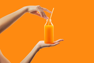 Papiers peints Jus, Sirop Female hands holding bottle with straw of fresh detox orange juice