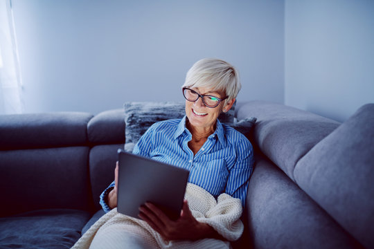 Beautiful smiling blonde caucasian senior woman sitting on sofa in living room and using tablet for internet surfing.