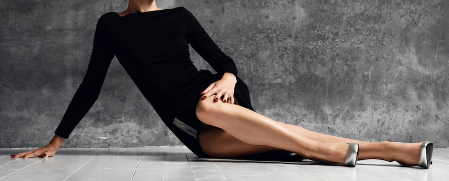 Woman lying on a floor with long gorgeous legs on dark in black little dress