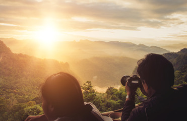 couple taking pictures of mountain landscape at sun rise  beautiful