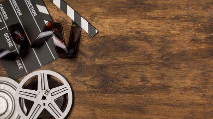 Negatives stripes with clapperboard and film reels on wooden desk