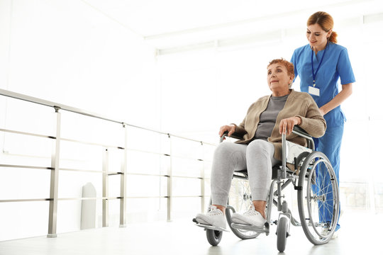 Nurse assisting elderly woman in wheelchair indoors. Space for text