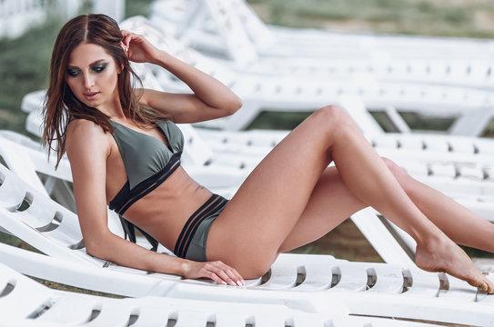 Attractive fashion woman in bikini lying on a chaise-longue, turn face