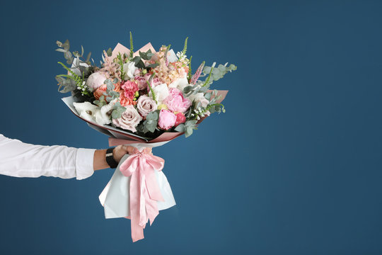 Man holding beautiful flower bouquet on blue background, closeup view. Space for text
