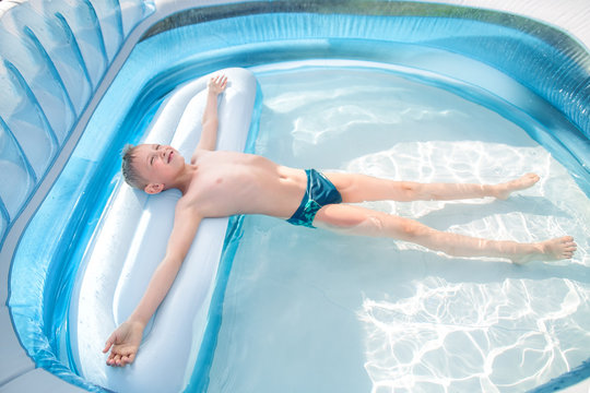 the boy lies relaxed in the pool