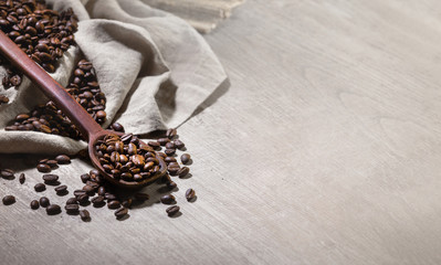 Coffee beans with spoon and burlap sack on reclaimed wood table top, space for ad design copy overlay, print and advertising