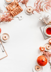 Autumn flat lay layout with copy space: tea setting, cakes, pastry and donuts with autumn flowers arrangement and pumpkin on white desktop background. . Top view. Frame