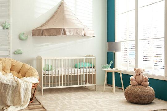 Cute nursery interior with comfortable crib near white wall