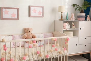 Cozy baby room interior with comfortable crib