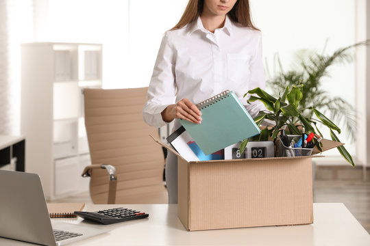Upset young woman packing stuff in box at office