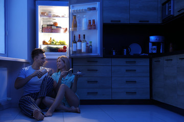 Happy couple eating near refrigerator in kitchen at night