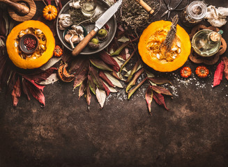 Autumn seasonal food background with halved pumpkin, knife , herbs and spices on dark rustic background with fall leaves. Top view. Border