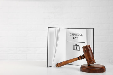 Book with words CRIMINAL LAW and gavel on table against white background. Space for text