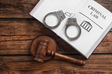 Book with words CRIMINAL LAW, handcuffs and gavel on wooden table, flat lay