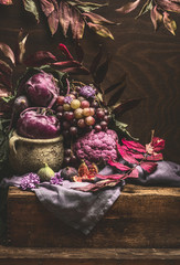 Still life with purple fruits and vegetables on wooden table with crockery, napkin and autumn leaves . Copy space for your design