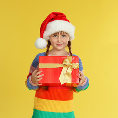 Cute little girl in Santa hat with Christmas gift on yellow background