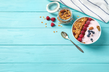 Tasty homemade granola served on blue wooden table, flat lay with space for text. Healthy breakfast