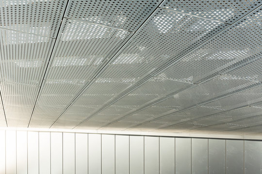 Diagonal view of metall grilles and round holes in metal ceiling surface, perforated panels