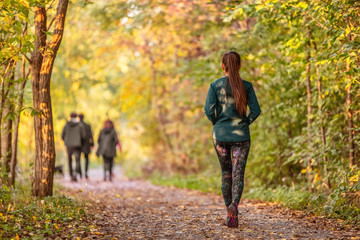 Woman walking in autumn forest nature path walk on trail woods background. Happy girl relaxing on active outdoor activity. Fotomurales